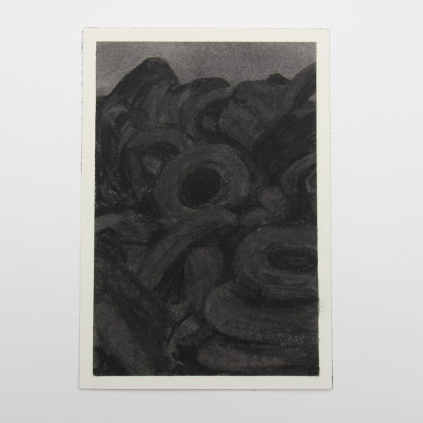 From a distance the drawing looks almost entirely black. When you move closer it reveals a dark landscape comprised of stacked rubber tires and a small area of dark sky all rendered in charcoal